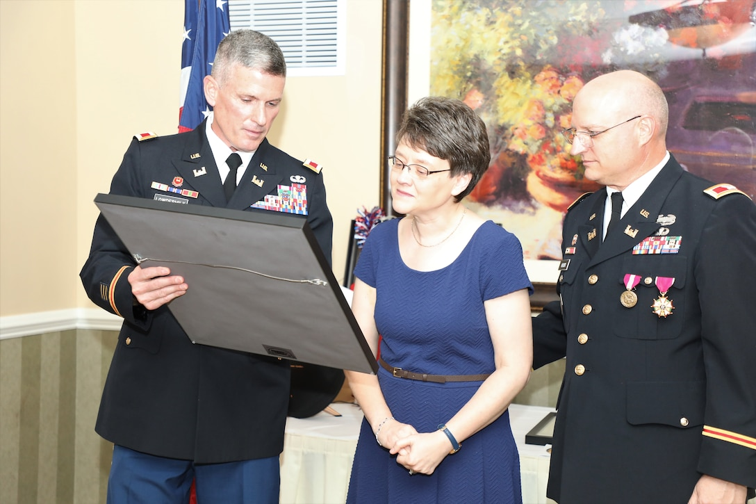 Army Reserve Col. Scott Lowdermilk, U.S. Army Corps of Engineers Transatlantic Division Director of Plans and Operations (left) presents a gift to Sally Heuser, the wife of Army Reserve Col. Todd M. Heuser, who retired July 13, 2019, after a 30-year military career, during a ceremony held in Winchester, Virginia.