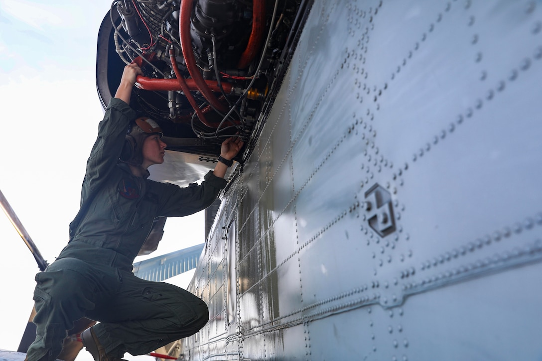 A sailor works on  a helicopter.