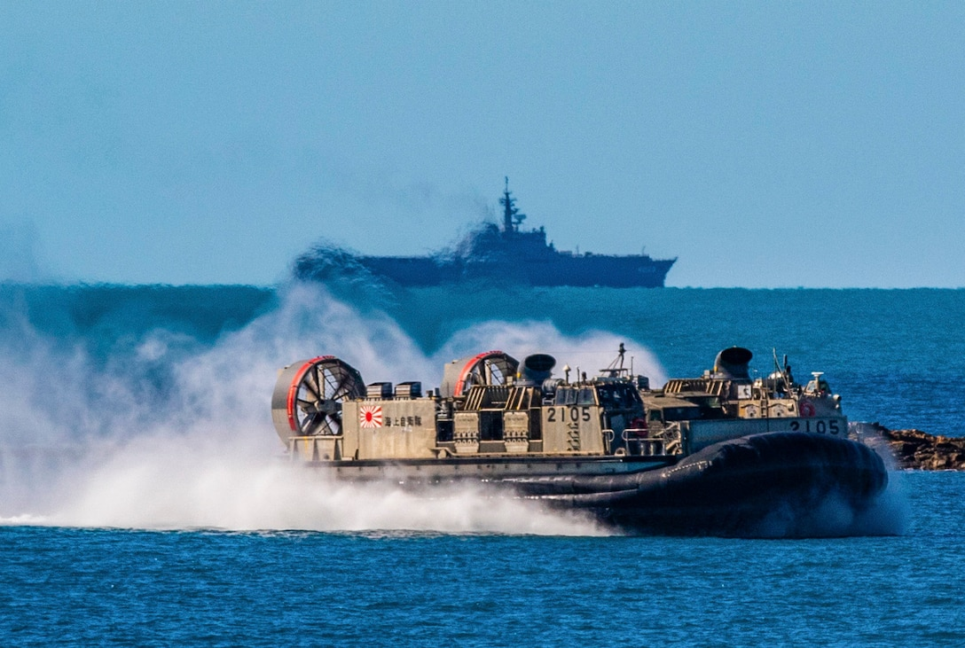 In front of the Japanese Ship Kunisaki, a landing craft, air cushion approaches Langham Beach, Queensland Australia, July 16, during Exercise Talisman Sabre 2019. Talisman Sabre 19 is a bilateral exercise that provides U.S. and Australian forces realistic and relevant training to strengthen regional security, peace and stability.