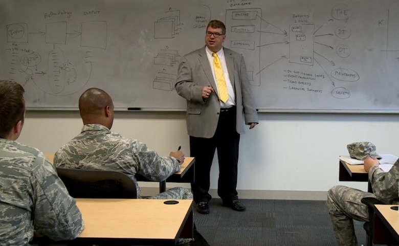 Dr. Michael Grimaila, professor and department head of the Department of Systems Engineering and Management at the Air Force Institute of Technology talking to students at one of the SEC courses at AFIT. (Courtesy photo)