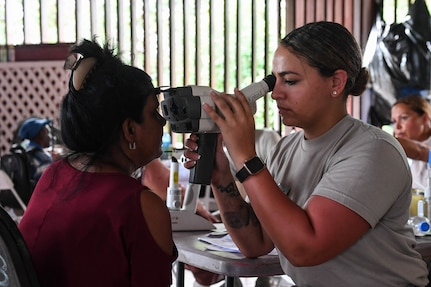 An optometry technician performs an eye exam.