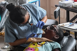 A dental technician performs an examination.