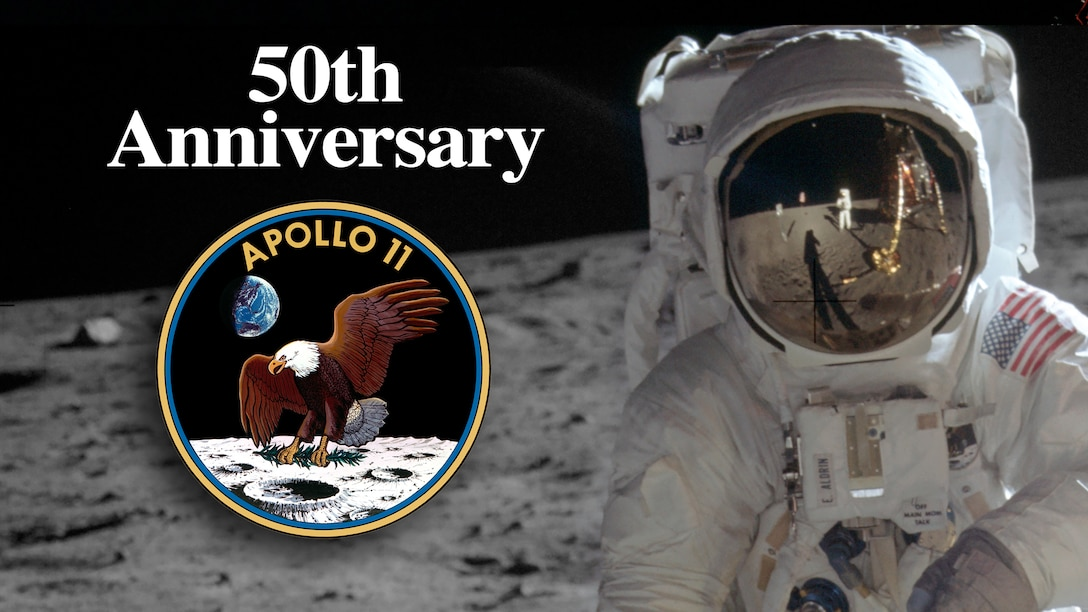 Astronaut Buzz Aldrin stands on the surface of the moon with the leg of the lunar module reflected in his visor. An Apollo II emblem is accompanied by the text 50th Anniversary.