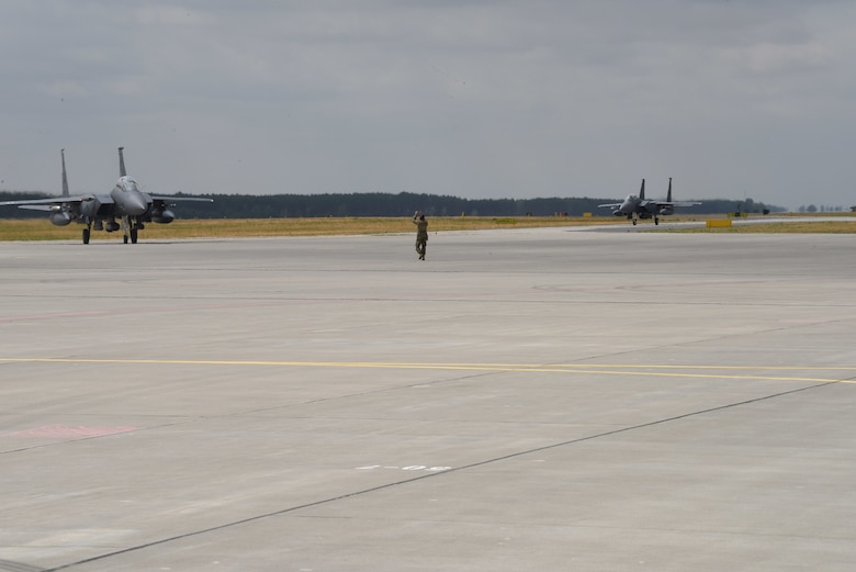 Two F-15 Strike Eagle aircraft deployed from the 336th Fighter Squadron, 4th Fighter Wing, Seymour Johnson Air Force Base, N.C., taxi on a runway during Operation Rapid Forge on Powidz Air Base, Poland, July, 16, 2019. Rapid Forge is a U.S. Air Forces in Europe-led mission to enhance readiness and test the ability to function at locations other than the main air bases.