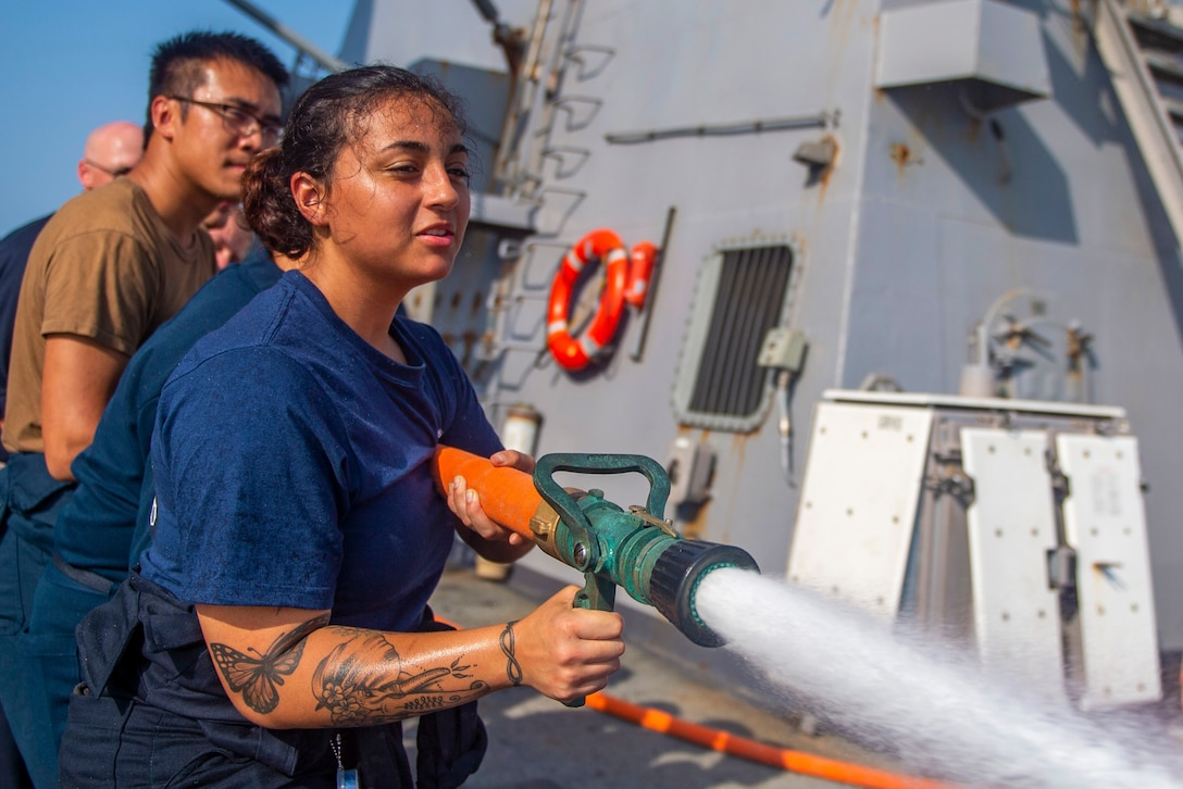 A group of sailors direct a water hose on a ship.
