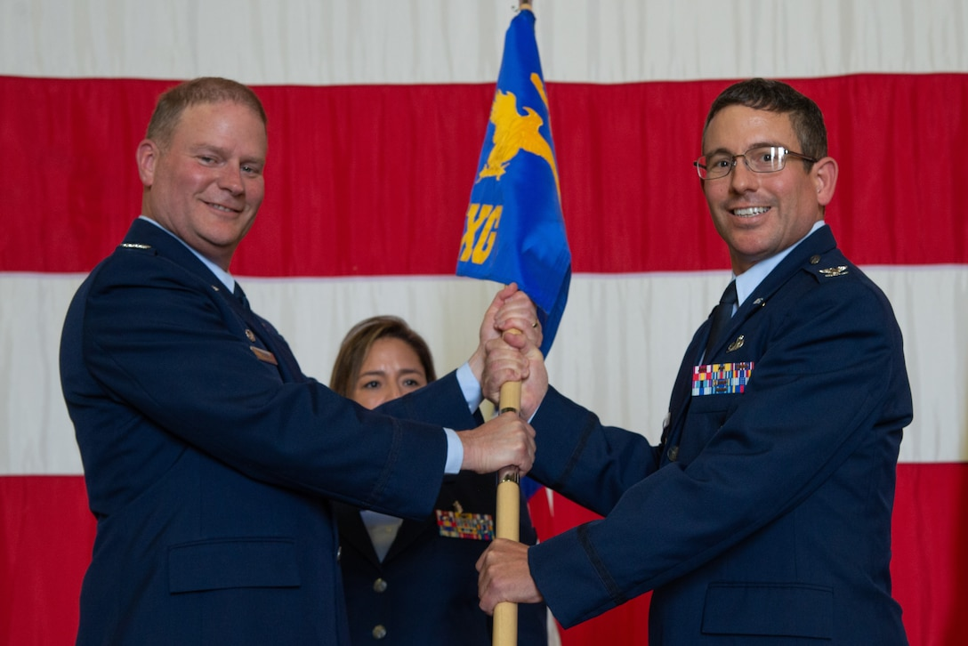 Col. James DeVere, the 302nd Airlift Wing commander, presents the 302nd Maintenance Group guidon to Col. Jordan Murphy, the new 302nd MXG commander, during a change of command ceremony July 14, 2019, at Peterson Air Force Base, Colorado. (U.S. Air Force photo by Staff Sgt. Justin Norton)