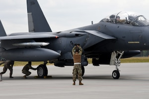 A U.S. Air Force member from the 336th Fighter Squadron, 4th Fighter Wing, Seymour Johnson Air Force Base, N.C., gives taxi instructions to an F-15 Strike Eagle fighter jet pilot during Operation Rapid Forge on Powidz Air Base, Poland, July, 16, 2019. Operation Rapid Forge is intended to enhance interoperability with NATO allies to improve combined operational capabilities.
