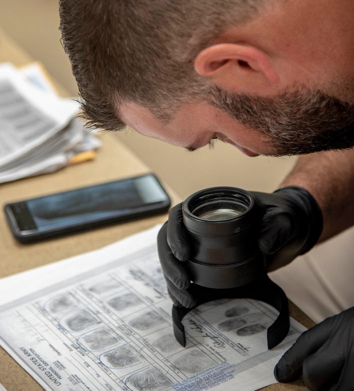 Bryan Thomas Johnson, Federal Bureau of Investigation major incident program manager, examines a fingerprint for a match at the Armed Forces Medical Examiner System, Dover Air Force Base, Del., July 9, 2019. Remains found on Colony Glacier are fingerprinted for possible identification. (U.S. Air Force photo by Staff Sgt. Nicole Leidholm)