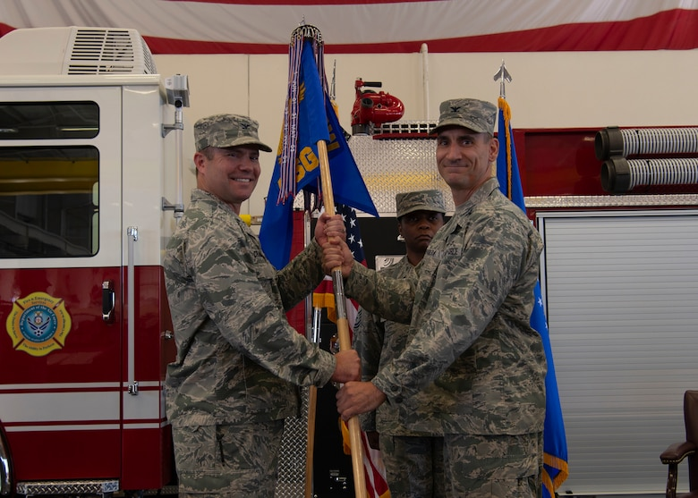 U.S. Air Force Col. Cavan Craddock, commander 99th Air Base Wing, passes the guidon to Col. Anthony Figiera, commander 99 Mission Support Group, during the 99th MSG change of command ceremony on Nellis Air Force Base, Nev., July 7, 2019. The 99th MSG has more than 3,000 military personnel and supports over 479,000 customers annually. (U.S. Air Force photo by SrA Stephanie Gelardo)