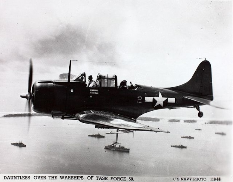 An SBD Douglas dive bomber flying over Task Force 58 in the Marshall Islands on the way to attack targets in the Marianas on June 15, 1944, the day U.S. forces landed on Saipan. It proved to be an excellent Navy scout plane and dive bomber and sank more enemy shipping in the Pacific War than any other Allied aircraft.