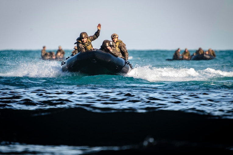 Marines ride in three rubber boats.