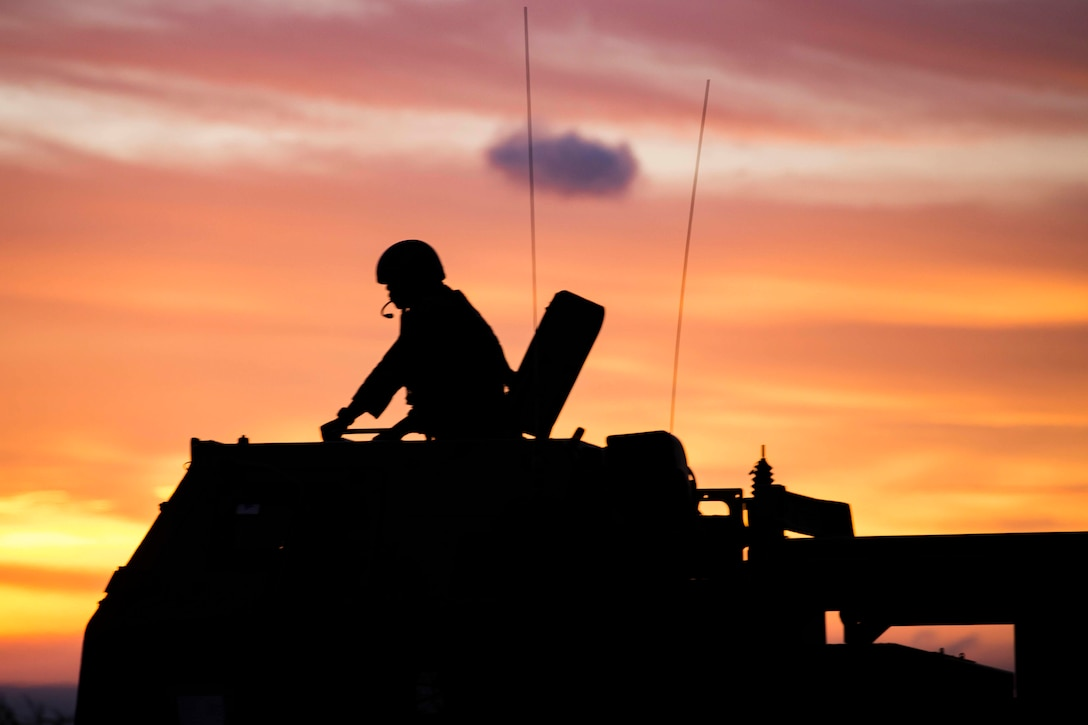 A silhouette of a Marine on top of a military vehicle.