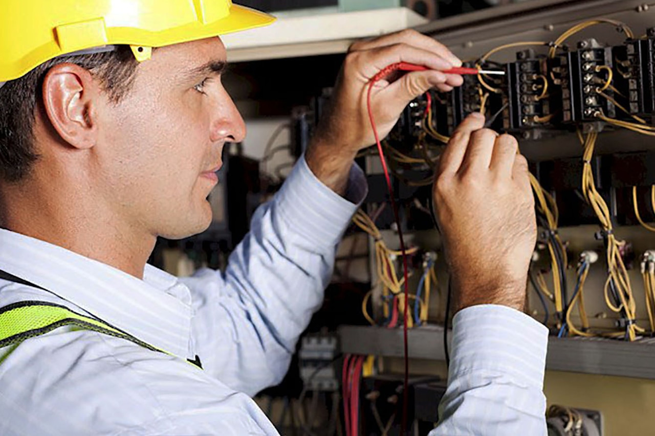 Electrician works on circuit panel.