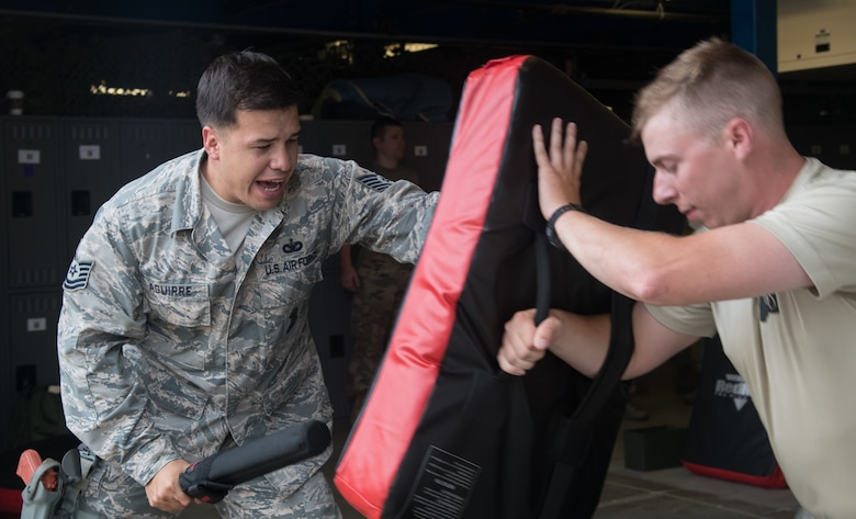 Tech. Sgt. Zeferino Aguirre, 932nd Security Forces Squadron unit training manager , simulates striking an adversary during baton training July 14, 2019, at Scott Air Force Base, Illinois. He is responsible for creating and implementing a training plan such as use of force or baton training. Training involves classroom lecture and hands on skills. (U.S. Air Force photo by Senior Airman Melissa Estevez)