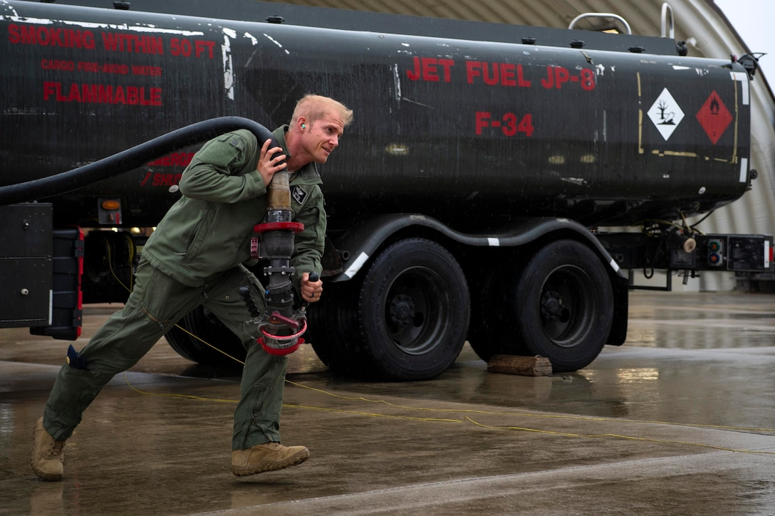 An airman drags a hose over his shoulder.