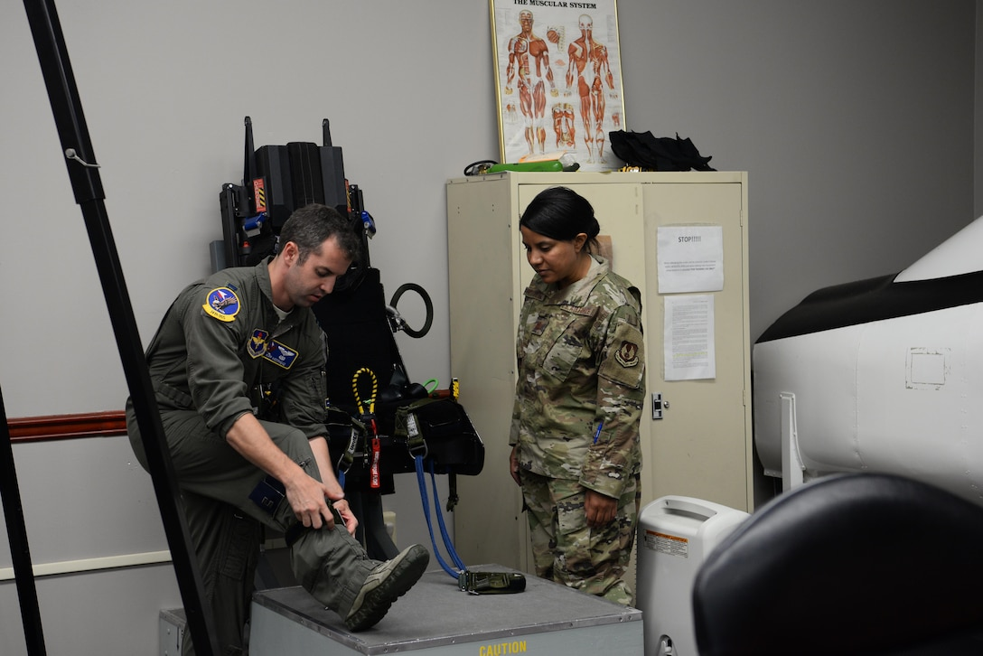 Capt. Kip Moorhead, 14th OSS operations flight commander, shows Maj. Saily Rodriguez, the Human Systems Program Office female fitment program manager, how to strap on safety belts in a T-38 Talon seat, July 11, 2019, on Columbus Air Force Base, Mississippi. Rodriguez is a female fitment program manager whose job is to research and develop, test, evaluate and manage aircrew flight equipment.