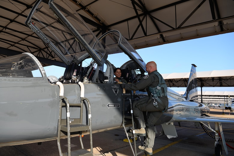 Maj. Saily Rodriguez, the Human Systems Program Office female fitment program manager, sits in a T-38 Talon while Maj. Ryan Claussen, 50th Flying Training Wing chief of instructor pilots, climbs a ladder, July 12, 2019, on Columbus Air Force Base, Mississippi. Rodriguez went on the incentive flight to test the equipment and to try out a disposable urinary relief device called the Traveljohn.