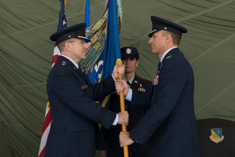 Lt. Gen. Jim Slife, Air Force Special Operations Command commander, hands the 27th Special Operations Wing guidon to Col. Robert Masaitis, incoming 27th SOW commander, during the change of command ceremony, July 17, 2019, at Cannon Air Force Base, N.M. Masaitis took command from the outgoing commander, Col. Stewart Hammons. (U.S. Air Force photo by Senior Airman Vernon R. Walter III)