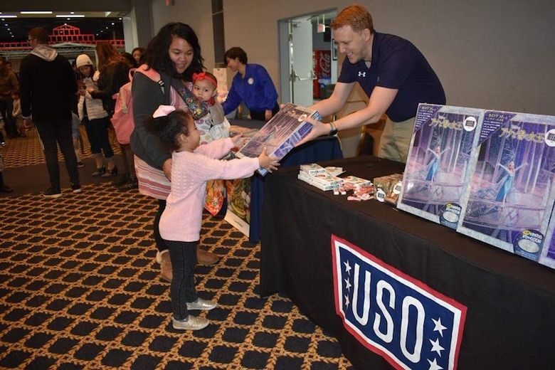 Nathan Evans, United Service Organizations field program manager, gifts a present to a young girl at a USO holiday event at Yokota Air Base, Japan, Dec. 10, 2017.