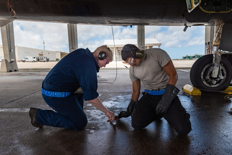 U.S. Air Force Airmen 1st Class Randall Petri, left, and Alfredo Cruz Perez, right, F-15C Eagle assistant dedicated crew chiefs assigned to the 44th Aircraft Maintenance Unit, perform a joint oil analysis program July 2, 2019, on Kadena Air Base, Japan. Members of the 44th AMU are vital to the 18th Wing's mission, as they spearhead the protection of a free and open Indo-Pacific region by keeping its aircraft in the air. (U.S. Air Force by Senior Airman Cynthia Belío)