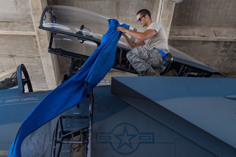 U.S. Air Force Airman 1st Class Christopher Nelson, F-15C Eagle avionics specialist assigned to the 44th Aircraft Maintenance Unit, attaches a protective cover on an aircraft July 2, 2019, on Kadena Air Base, Japan. The life of a dedicated crew chief requires non-stop dedication, day and night, to maintain air-to-air combat superiority. (U.S. Air Force photo by Senior Airman Cynthia Belío)