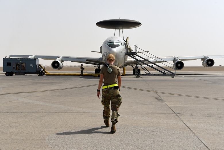 Crew chiefs assigned to the 380th Expeditionary Aircraft Maintenance Squadron perform a foreign object debris walk prior to an E-3 Sentry taxiing for flight on Al Dhafra Air Base, United Arab Emirates, June 26, 2019.