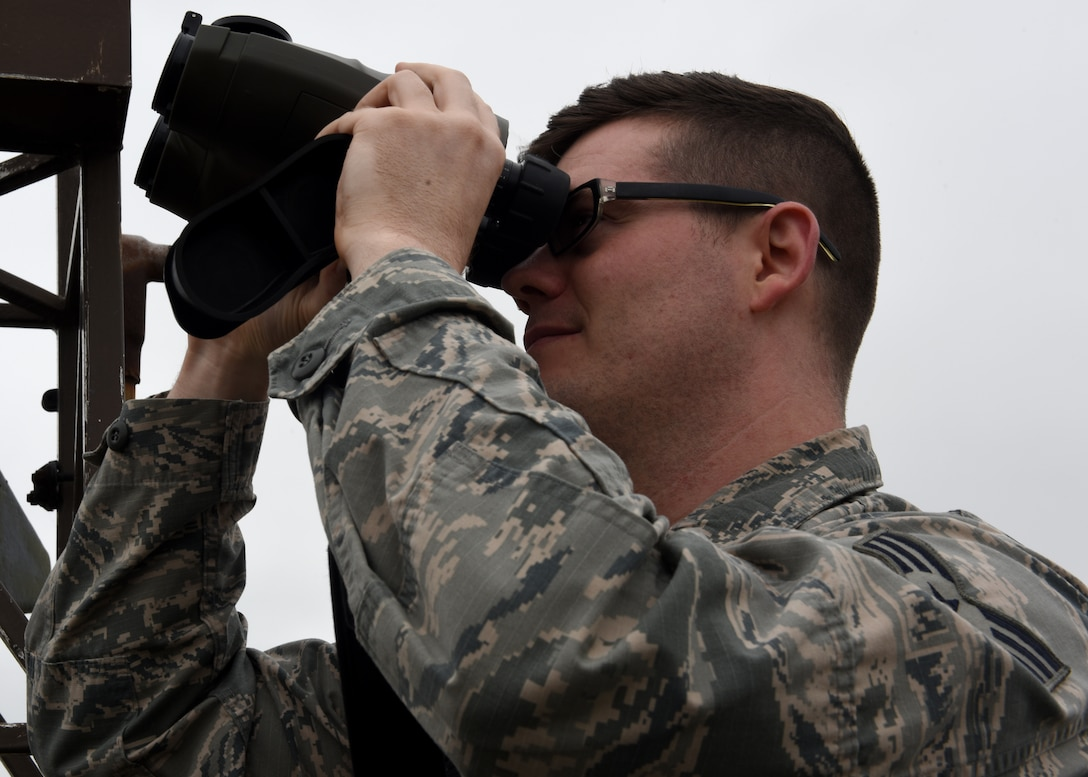 U.S. Air Force Senior Airman Michael Scanlan, 48th Operations Support Squadron weather specialist, uses a laser rangefinder at Royal Air Force Lakenheath, England, June 26, 2019. The Weather Flight use specialized tools to create an accurate forecast for Liberty Wing personnel. (U.S. Air Force photo by Airman 1st Class Rhonda Smith)