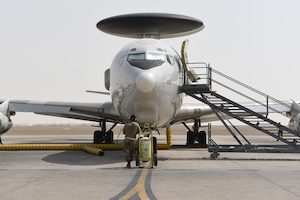 A crew chief assigned to the 380th Expeditionary Aircraft Maintenance Squadron waits in front of the E-3 Sentry on Al Dhafra Air Base, United Arab Emirates, June 26, 2019.