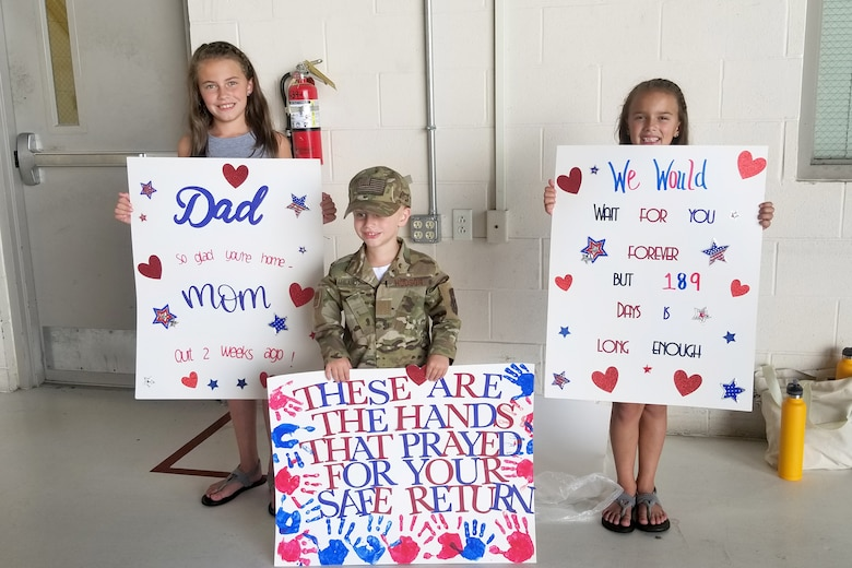 Charlee, Hudson and Mila Morris pose with signs July 15, 2019 at Grissom Air Reserve Base, Indiana while waiting for their father, Master Sgt. Michael Morris, to return home from his deployment. Their father along with 15 other Airmen were greeted and flown home by leadership after arriving at the Baltimore-Washington International airport. (U.S. photo/Ben Mota)