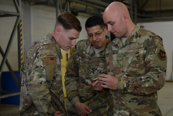 U.S. Air Force Staff Sgt. Zachary Tingen, 86th Maintenance Squadron aircraft fuel systems craftsman, shows a coin to his colleagues on Ramstein Air Base, Germany, July 15, 2019. Tingen received the coin just minutes prior for leading his team through cross utilization training.