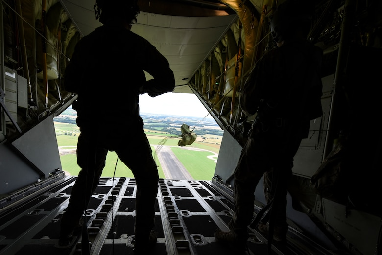 Two U.S. Air Force loadmasters from the 67th Special Operations Squadron, RAF Mildenhall, England, watch as a payload deploys from the back of a MC-130J Commando II aircraft July 11, 2019, during the 67 SOS Strix Rodeo training.
