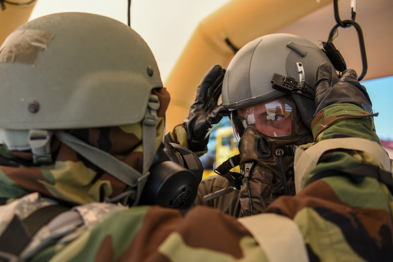 A flight equipment specialist for the Kentucky Air National Guard's 123rd Airlift Wing assists an aircrew member at a chemical contamination control point during an exercise at the Alpena Combat Readiness Training Center in Alpena, Mich., June 23, 2019. The exercise, called Charred Barrel, tested the wing's ability to mobilize, fly to a remote site, and operate in a hostile environment. (U.S. Air National Guard photo by Staff Sgt. Joshua Horton)