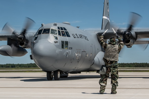 An aircraft maintainer wearing a chemical warfare defense ensemble directs a Kentucky Air National Guard C-130 Hercules aircraft to its parking spot at the Alpena Combat Readiness Training Center in Alpena, Mich., June 23, 2019, during exercise Charred Barrel. The event tested the wing's ability to mobilize, fly to a remote site, and operate in a hostile environment. (U.S. Air National Guard photo by Staff Sgt. Joshua Horton)