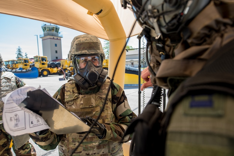 Hannah Nunley (left), flight equipment specialist for the Kentucky Air National Guard's 123rd Airlift Wing, assists an aircrew member at a chemical contamination control point during an exercise at the Alpena Combat Readiness Training Center in Alpena, Mich., on June 23, 2019. The exercise, called Charred Barrel, tested the wing's ability to mobilize, fly to a remote site, and operate in a hostile environment. (U.S. Air National Guard photo by Staff Sgt. Joshua Horton)
