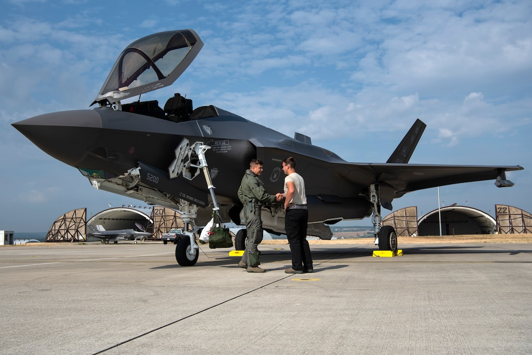 U.S. Air Force Capt. Joseph Walz, 421st Fighter Squadron F-35A Lightning II pilot, shakes hands with Airman 1st Class Cody Albert, 421st FS crew chief, during Operation Rapid Forge at Spangdahlem Air Base, Germany, July 18, 2019. Rapid Forge aircraft are forward deploying to the territory of NATO allies in order to enhance readiness and improve interoperability. Participation in multinational operations enhances the U.S. Air Force's relationship with partner militaries. (U.S. Air Force photo by Airman 1st Class Valerie Seelye)