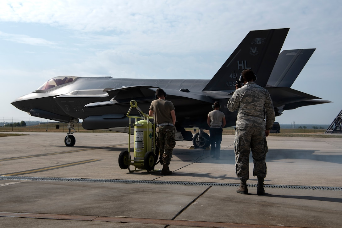U.S. Air Force Senior Airman Tyler McGaughey, 421st Fighter Squadron avionics specialist, Airman 1st Class Cody Albert, 421st FS crew chief, and Staff Sgt. David Sasak, 421st FS crew chief, prepare an F-35A Lightning II for launch during Operation Rapid Forge at Spangdahlem Air Base, Germany, July 18, 2019. Rapid Forge aircraft are forward deploying to bases in the territory of NATO allies. Training with multinational air forces during operations strengthens allied coalition forces. (U.S. Air Force photo by Airman 1st Class Valerie Seelye)