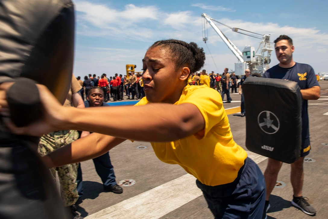 A sailor strikes a pad on deck of a ship while others look on.