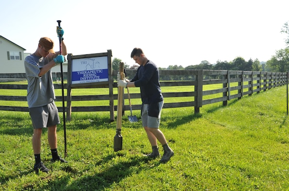 Air Force Academy Cadets Zack LaRocque, left, and Evan Place, right, dig post holes to place a sign at the Therapeutic Riding Institute. After a quality time with shovels, the duo were able to permanently place the Institute's sign at the property's entrance. LaRocque, Place and 18 fellow cadets travelled to Spring Valley, Ohio July 6, to volunteer with the institute ready its new location to begin operations. (U.S. Air Force photo/John Van Winkle)