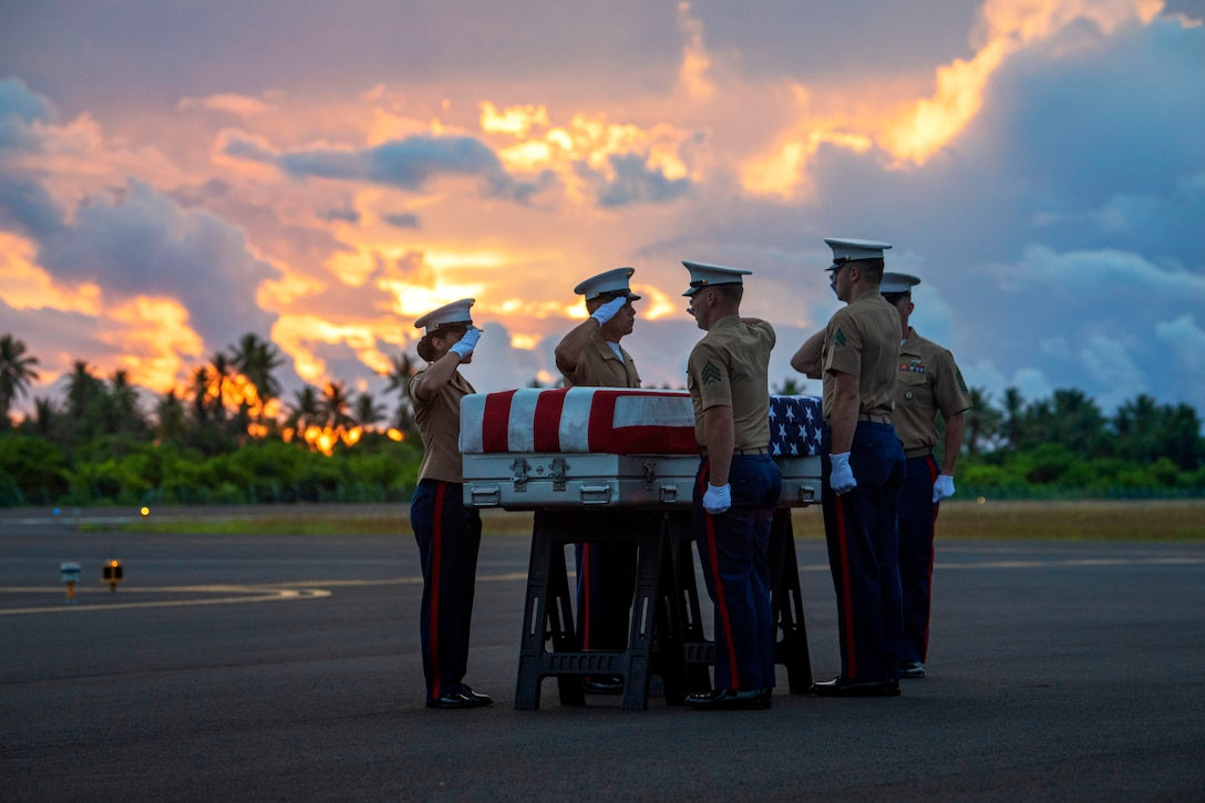 Marines salute a casket draped in American flag.