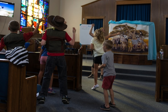 Children attending Vacation Bible School at Laughlin Air Force Base, Texas, dance to music in the opening portion of the night's activities on the week of July 8, 2019. The evening opened and closed with singing and dancing, and the children who attended not only colored in the daily coloring sheet for points toward their teams, but they also wrote poems about their VBS experience. (U.S. Air Force photo by Senior Airman Anne McCready)