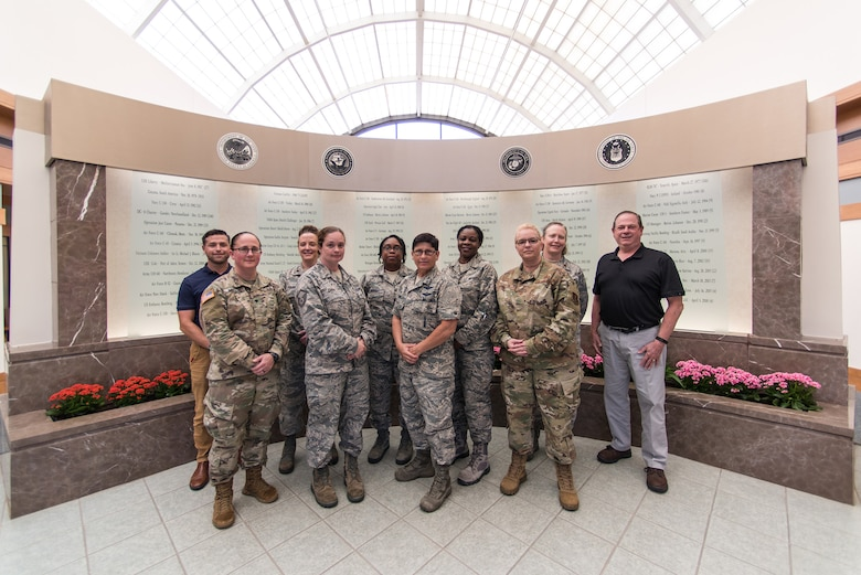Members of the Delaware Air National Guard 166th Airlift Wing and Delaware Army National Guard pose in front of the memorial wall in the lobby of the Dover Air Force Base Mortuary Affairs Operations Center June 27, 2019. Delaware National Guard members were invited to tour Air Force Mortuary Affairs Operations and Air Forces Medical Examiner System laboratories. (U.S. Air National Guard photo by Staff Sgt. Katherine Miller)