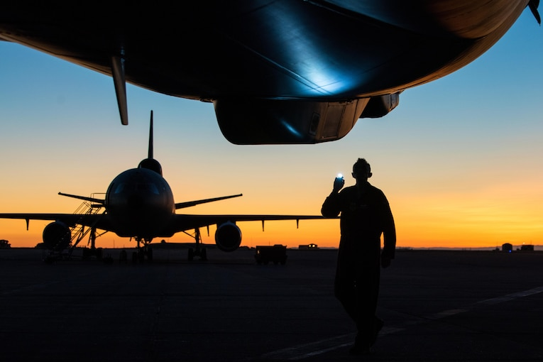 An airmen uses a flashlight to look at an aircraft.