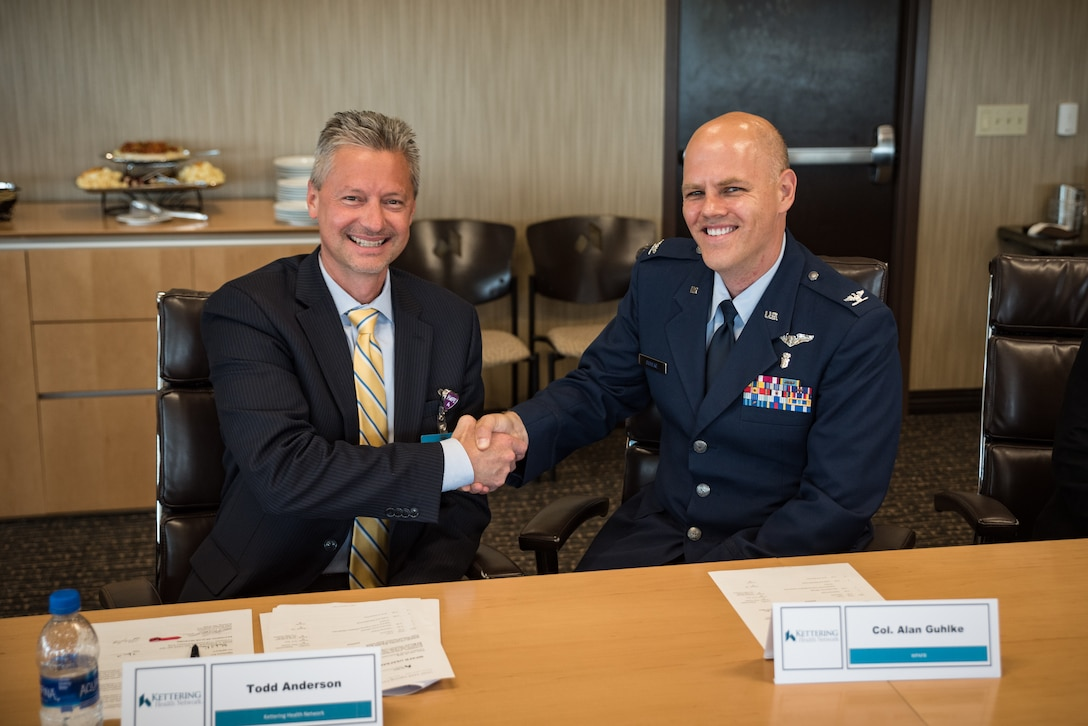 Todd Anderson, executive vice president for Kettering Health Network, and Col. (Dr.) Alan Guhlke, chair, En route Care Training Department at USAFSAM, shake hands after signing a training affiliation agreement July 15 authorizing medical personnel from the USAFSAM to partner together with Kettering Health Network to enhance the readiness of Air Force medical service personnel. (U.S. Air Force photo/Richard Eldridge)