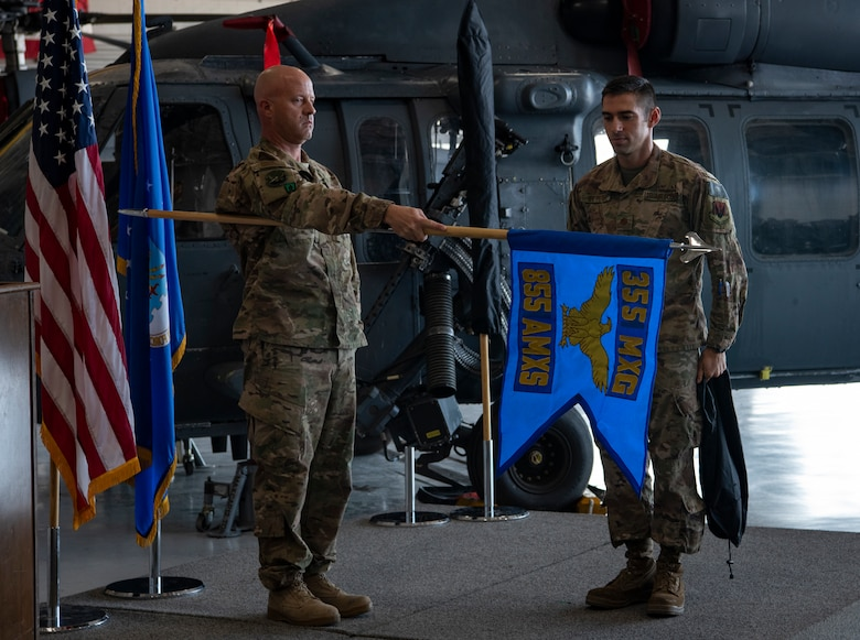 Chief Master Sgt. Jason A. Breitmaier, superintendent 855th Aircraft Maintenance Squadron (AMXS) and Maj. Jonathan J. St Peter, commander 855th AMXS, unveil the 855th AMXS guidon at a redesignation ceremony at Nellis Air Force Base, Nev., Jul. 11, 2019. The 855th AMXS maintains and repairs HH-60G Pave Hawk rescue helicopters here at Nellis. (U.S. Air Force photo by Airman 1st Class Dwane R. Young)