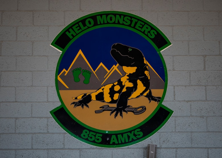"""The 855th Aircraft Maintenance Squadron unveils their new patch and mascot at a redesignation ceremony at Nellis Air Force Base, Nev., Jul. 11, 2019. Their mascot the """"Helo Monster"""" a combination of helicopter and gila monster, a desert reptile native to southern Nevada and Arizona, representing Nellis AFB and the 355th Maintenance Group, Davis-Monthan AFB, Arizona. Black and yellow represent day and night as the squadron operates 24 hours a day. The green feet on the mountain represent the rescue community and the adverse terrain in which they operate. (U.S. Air Force photo by Airman 1st Class Dwane R. Young)"""