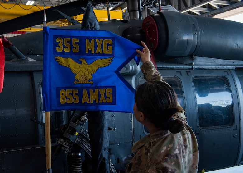 Capt. Linh P. Tran, Helicopter Maintenance Unit officer-in-charge, 855th Aircraft Maintenance Squadron (AMXS), looks at the new 855th AMXS guidon at a redesignation ceremony at Nellis Air Force Base, Nev., Jul. 11, 2019. The 855th AMXS maintains HH-60G Pave Hawk rescue helicopters, whose primary mission is to conduct day or night personnel recovery operations in hostile environments. (U.S. Air Force photo by Airman 1st Class Dwane R. Young)