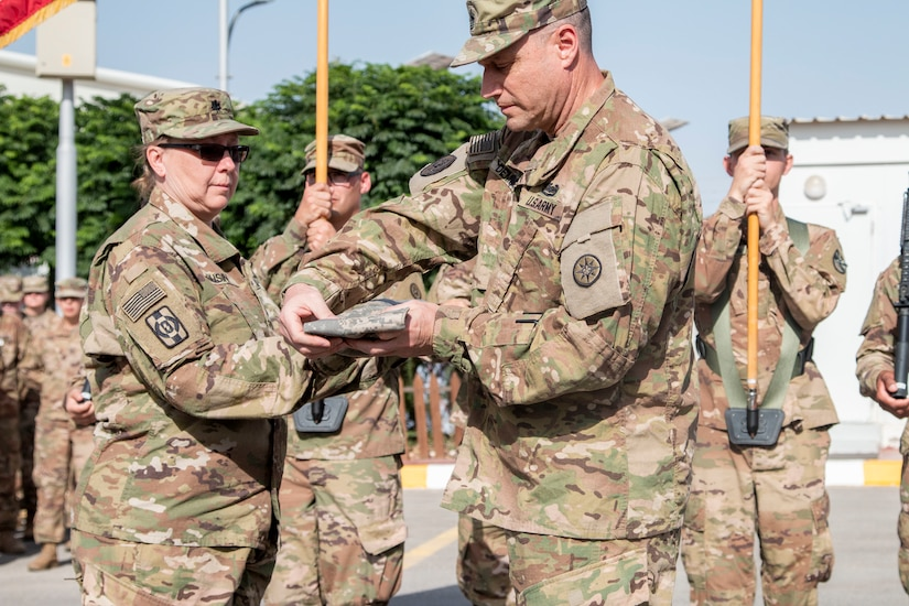 U.S. Army Lt. Col. Theresa Rusin (left), incoming deputy commanding officer for Area Support Group Jordan (ASG-J) and Command Sgt. Maj. John DeMarco, incoming senior enlisted advisor for ASG-J, uncase the colors of the 655 Regional Support Group, Army Reserve unit based out of Westover Air Reserve Base, signifying the official assumption of command from the 198 RSG, Arizona National Guard on July 18, 2019 at the Joint Training Center.