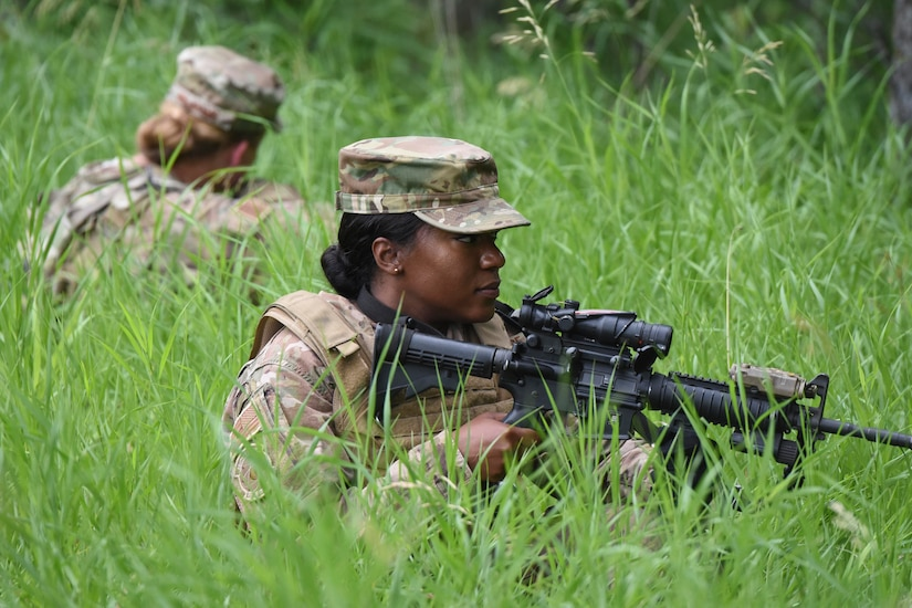 An airmen sits in the grass holding a weapon while another airmen sits behind