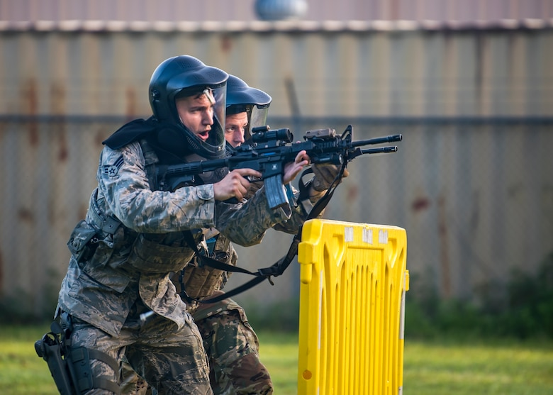 "Senior Airman Kyle Macintyre and Staff Sgt. Christian Bertram, both 23d Security Forces Squadron patrolmen, advance their position during a training exercise, July 15, 2019, at Moody Air Force Base, Ga. The ""Shoot, move, communicate"" training exercise put participants through practice maneuvers taking turns providing cover fire while others advanced on the enemy. Airmen learned how to shoot, move and communicate to build confidence in themselves, their wingmen and with their weapons. (U.S. Air Force photo by Airman 1st Class Eugene Oliver)"