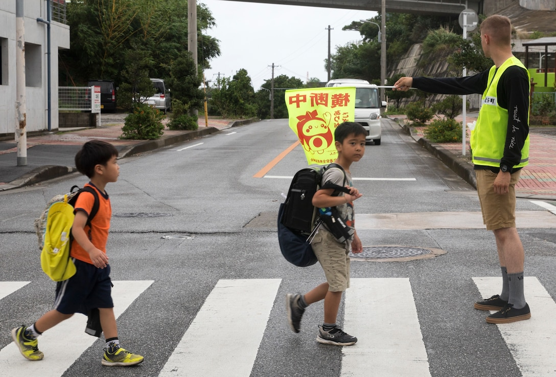 U.S. Marine Corps Lance Cpl. Timothy Silva guides local elementary school children through a crosswalk July 18, 2019. Crossing guard duty is one of the multiple roles conducted by volunteer Marines on camp guard duty.